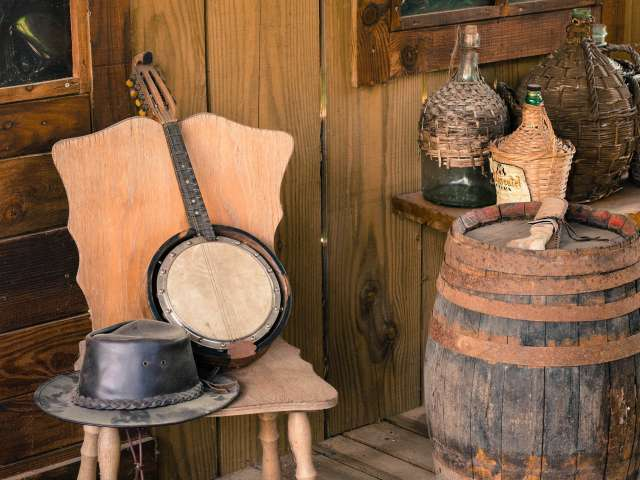 A banjo and rustic well-worn leather hat rest on a chair on a rustic cabin porch.