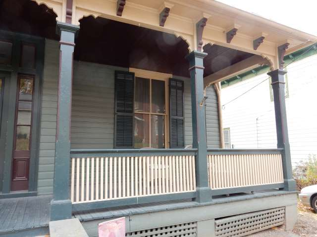 The front porch of historic house, painted in white and blue.