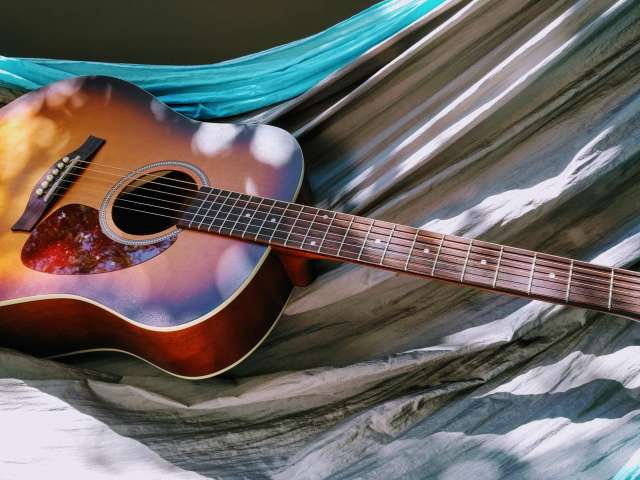 A rich-toned acoustic guitar rests on the ground, surrounded by colorful textiles.