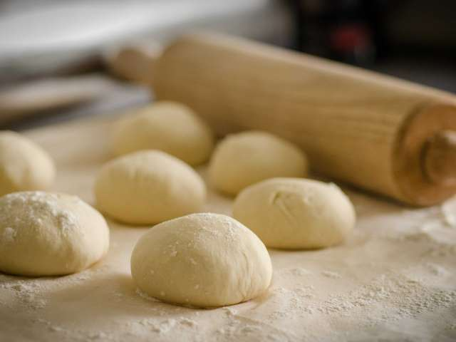 Balls of dough rest on a counter top with a rolling pin.