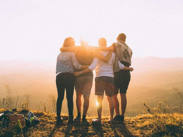 Four people embrace as they look out over a lovely sunset.