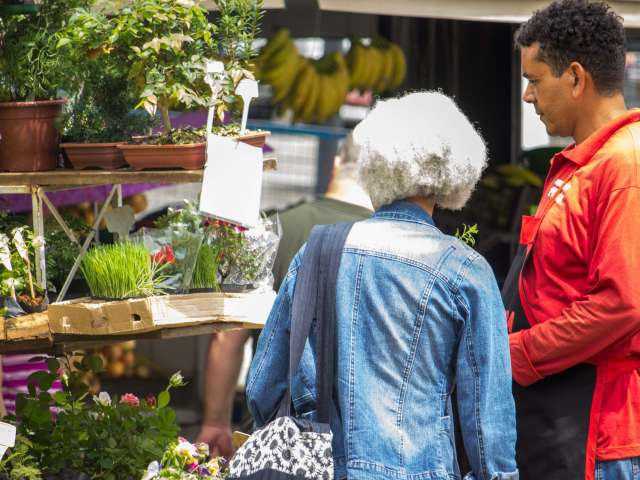 An older woman and a man look at produce in a market.
