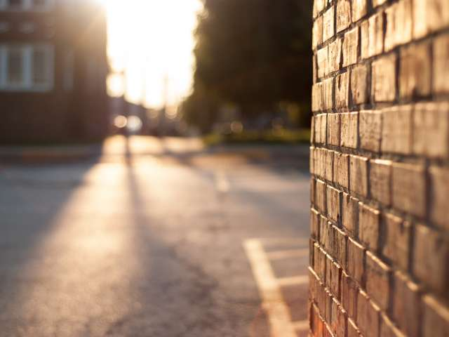 A close-up view of a brick wall, leading out to a small-town street.