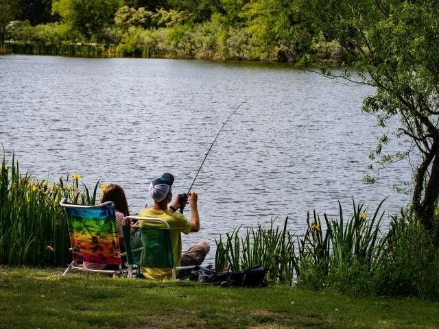 Two young people sit in lawn chairs by a lake and fish from the shore.