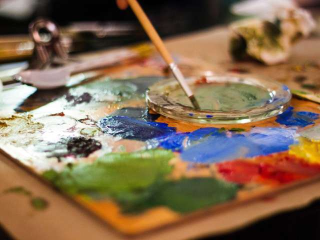 A messy and colorful paint palette with an artist's brush dipped into green paint.