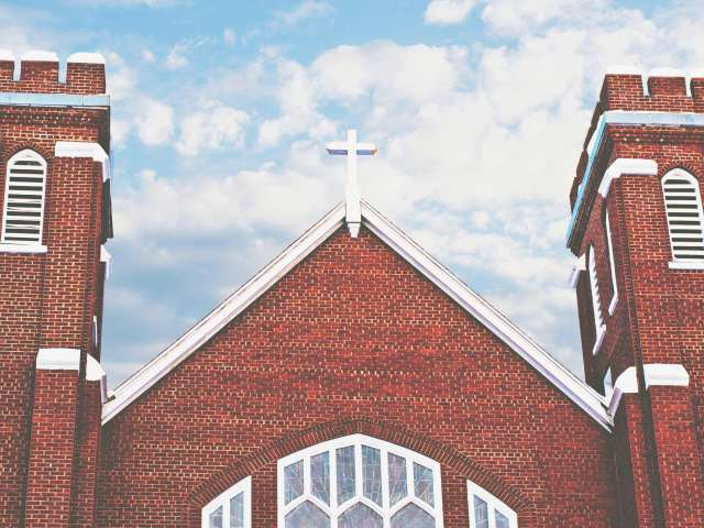 The central steeple of red brick church is flanked by two towers.