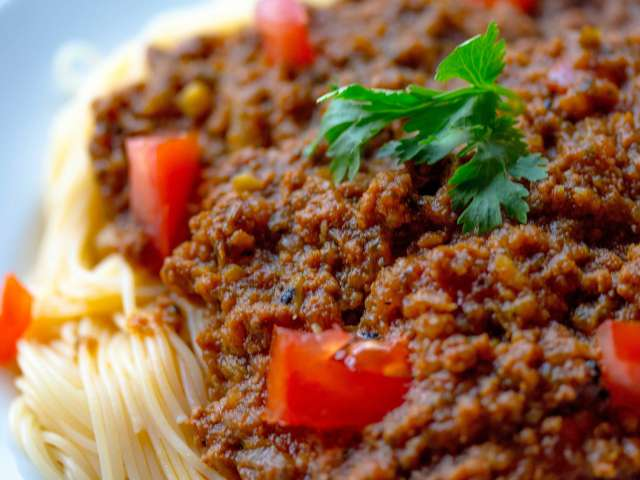 A close-up view of a plate of noodles with beef spaghetti sauce and chunky tomatoes.
