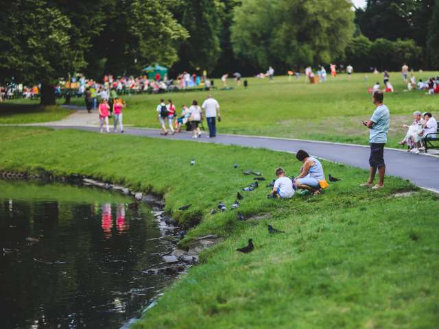 People walk on a paved park path while others sit by a pond on a summer day.