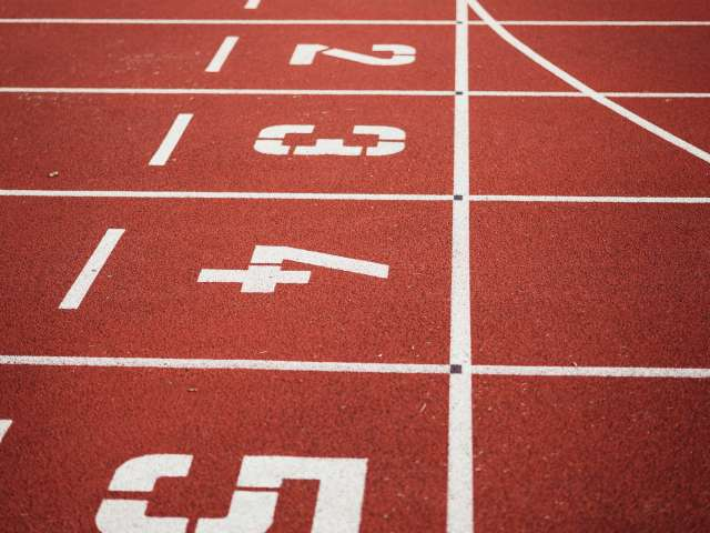 A close up of a track-and-field track with the numbers in white letters on the lanes.