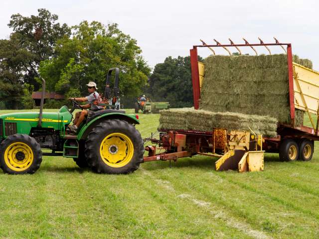 A man driving a large green tractor pulls a load of hay.