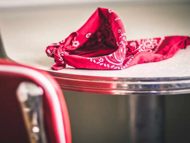 A red bandana rests on a table in a diner.
