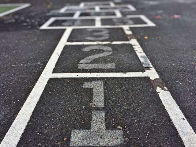 A hopscotch court painted onto black asphalt.