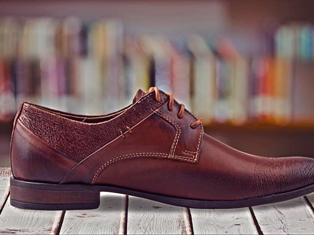 A man's dress shoe rests on a wooden table.