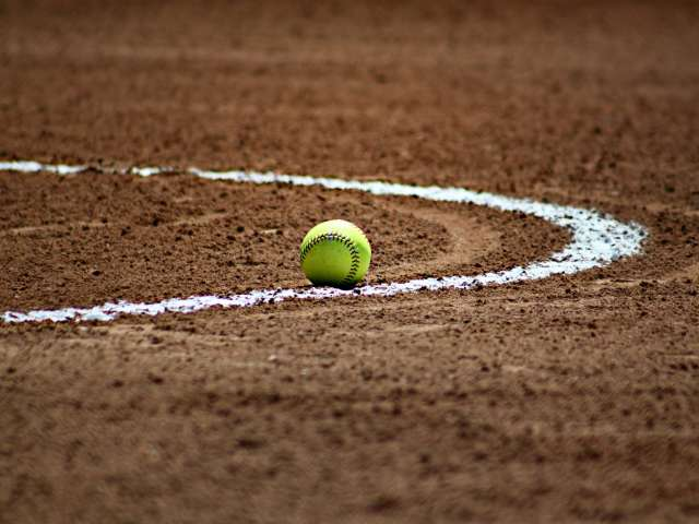 A yellow softball rests on a dirt field, marked with white lines.