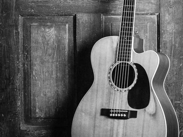 Black and white photo of an acoustic guitar, leaning up against an old door.