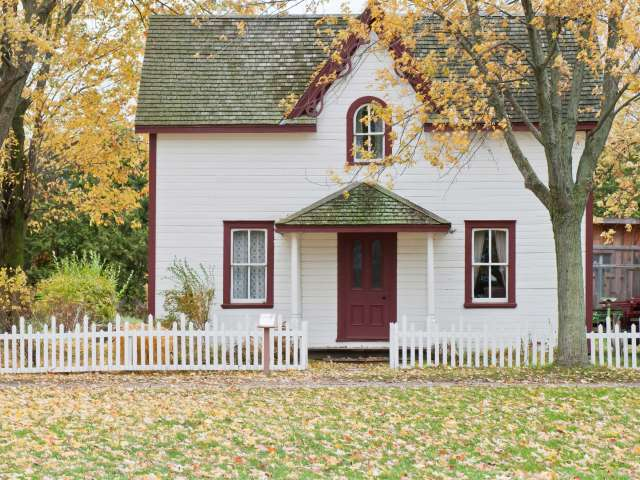 A small, quaint house in the country during autumn.