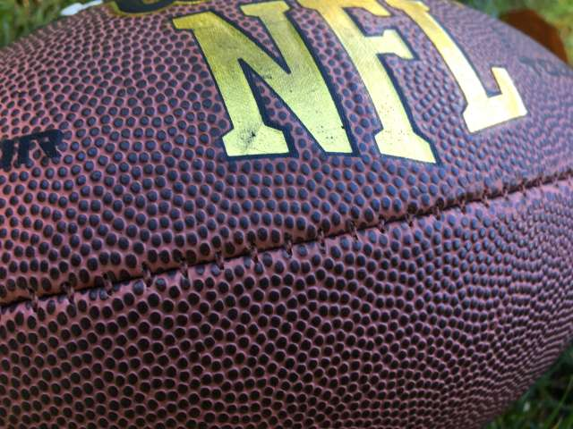 An detail of a football with the letters, NFL, in gold lettering.