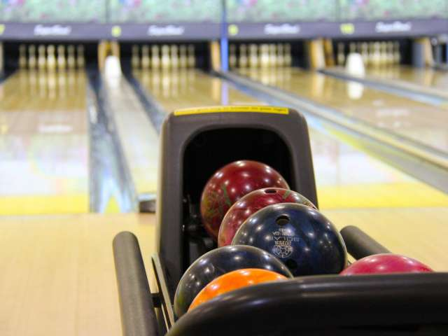 Colorful bowling balls in a brightly lit bowling alley.