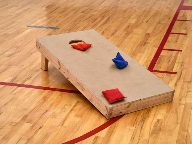 A wooden corn hole board with three bean bags on it in a school gymnasium.