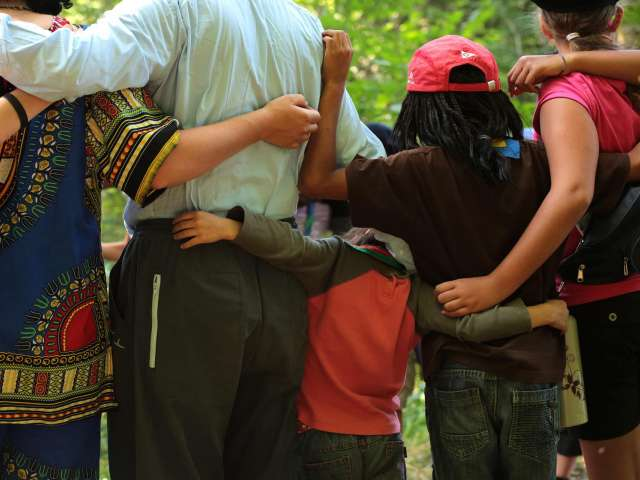 A group of young friends put their arms around each other in a camp setting.