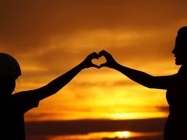 Silhouetted by a sunset, two people hold their hands in the shape of a heart.