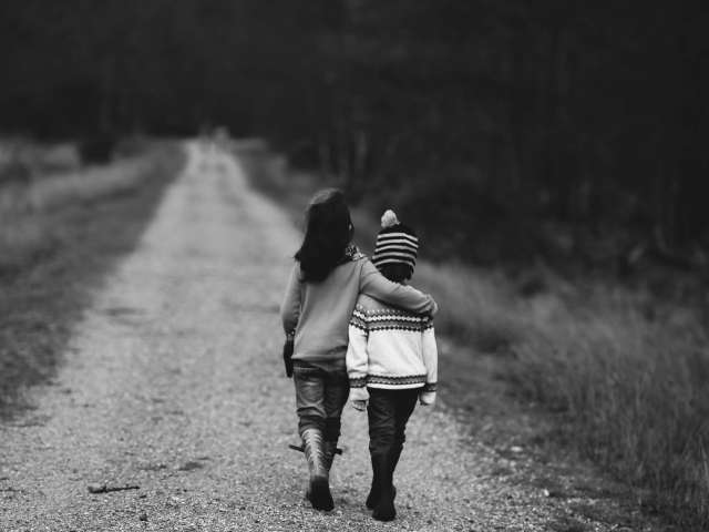 Two children walk hand-in-hand down a country road.