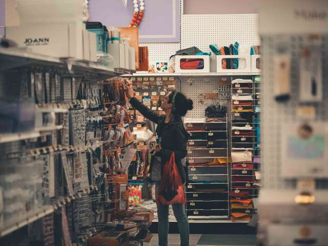 A woman looks for items on the shelves of a hardware store.