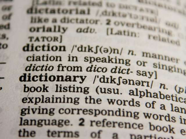 Close-up view on a page of the dictionary, focusing on the word 'dictionary.'