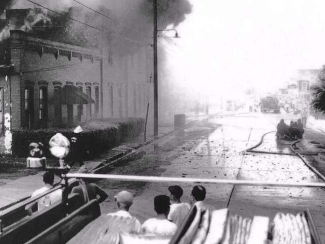 A vintage photo of a fire blazing in a building as people look on.