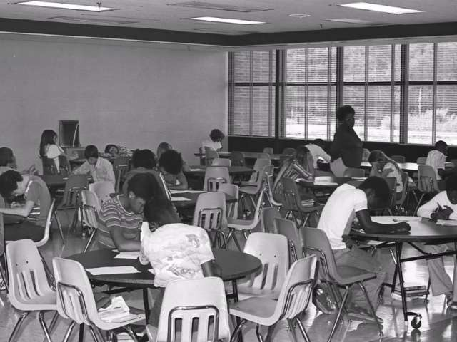 A vintage photo of African American children in a classroom space with small chairs and tables.