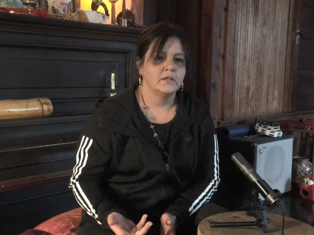 A woman with brown hair and a black running jacket sits in front of a microphone in her home.