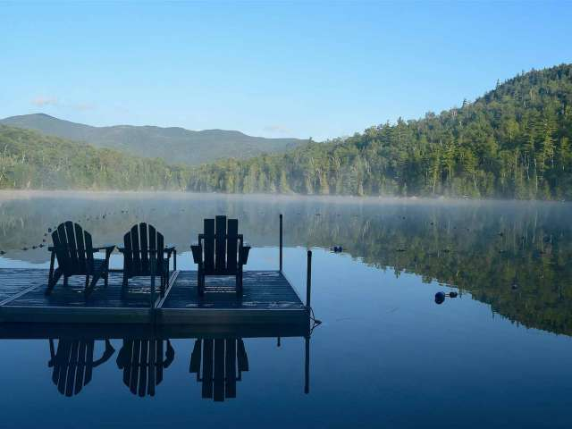 A serene lake surrounded by mountains with a dock and three chairs facing the lake.