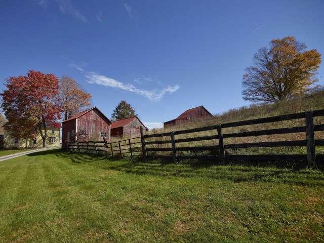 A rail fence runs along a grassy path toward several barns on a country lane.