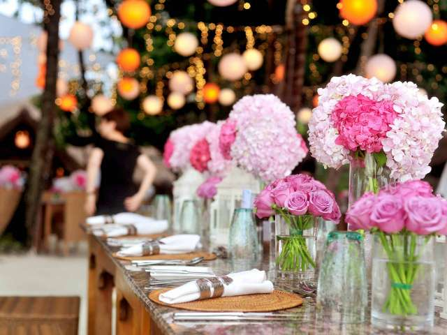 An outdoor party setting with various pink flowers in glass vases on a table.