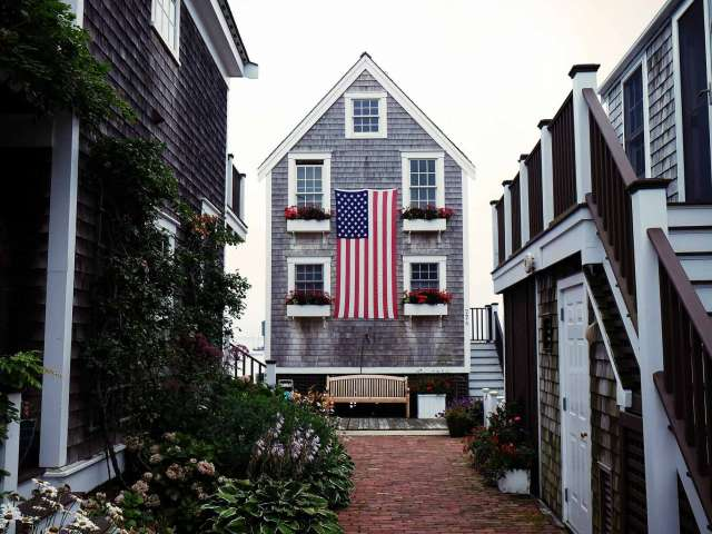 A New England-style gray shingle house with a large American flag on a narrow path leading to the water.