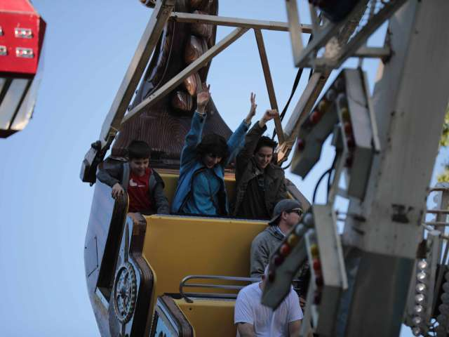 Thrill seekers put their hands in the air as they ride a swinging amusement park ride.