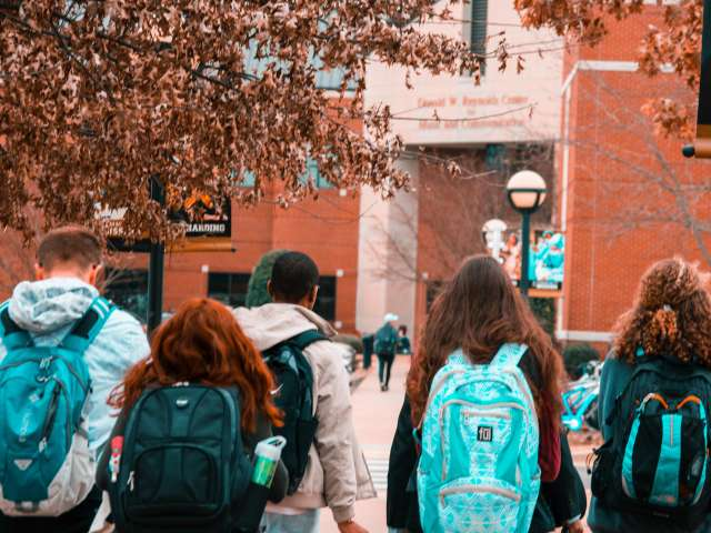 Teens wearing backpacks walk toward a school building in the fall.