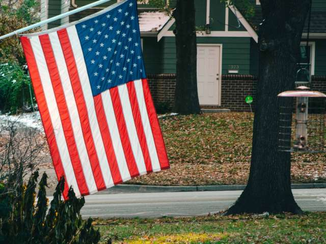 An American flag hangs in front of a green house in a neighborhood setting.