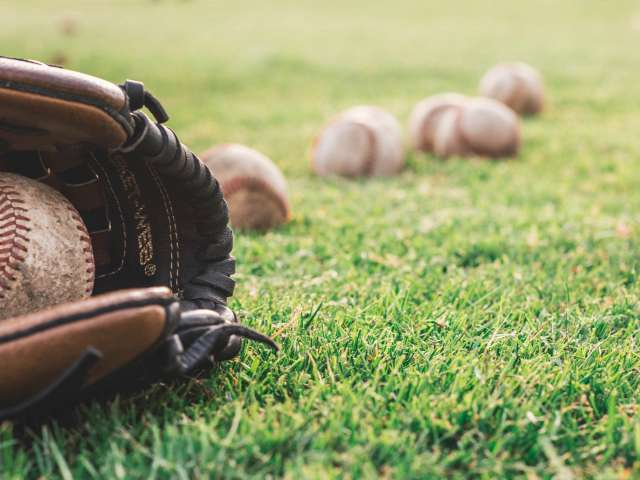 A baseball glove and a number of baseballs lay on a grassy field.