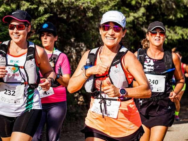 A group of women, wearing race bibs run on a trail.