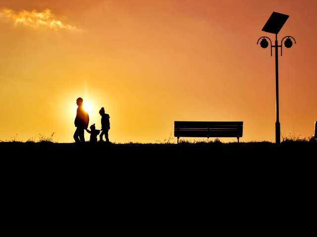 Three people walk at sunset near a park bench.