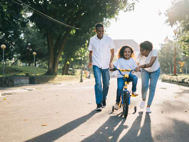 Parents help a young girl learn to ride a bike on a wide, tree-lined street.