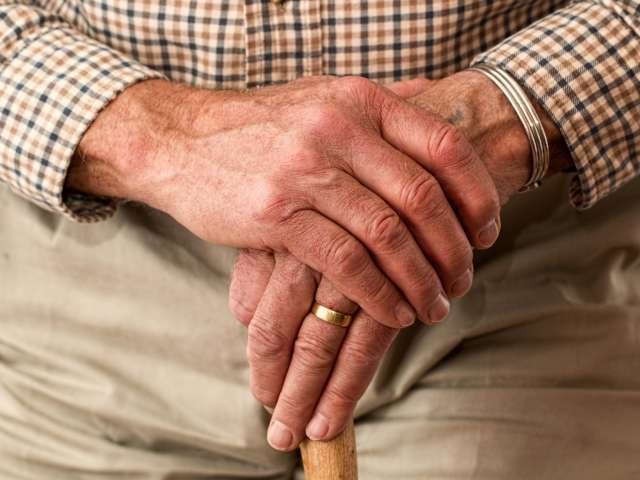 A close-up view of an elderly man's hands, holding the tip of a cane.