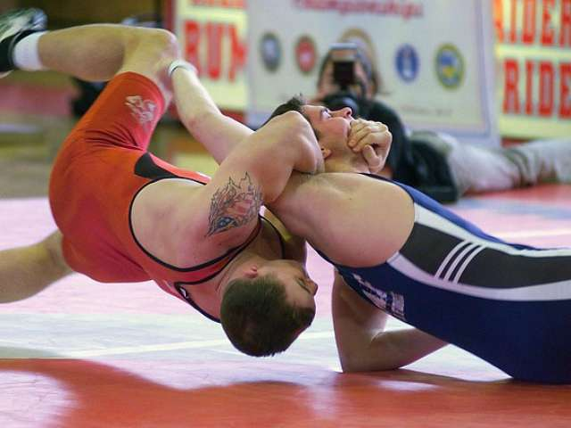 Two young men wrestle at a match.