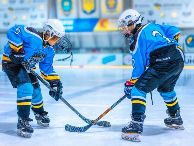 Two boys in ice hockey uniforms play on the ice.