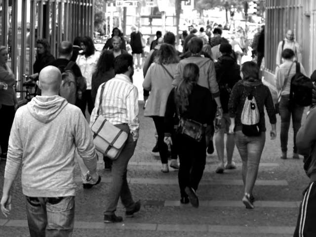 A black-and-white image of people walking down a crowded sidewalk.