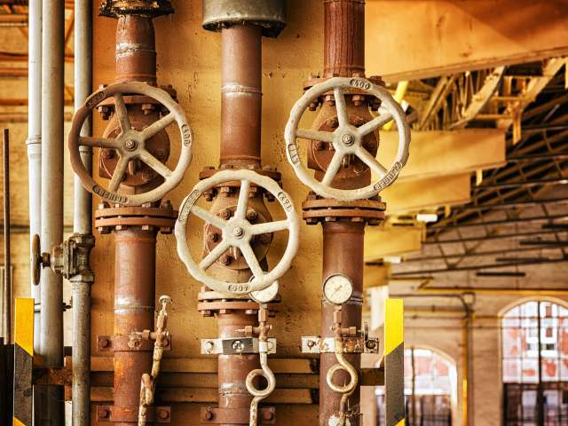 Three large, circular valves in a factory or industrial plant.