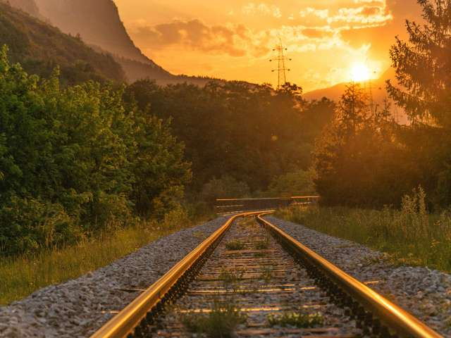 A birds-eye view of railroad tracks heading off into an idyllic, mountainous landscape at sunset.