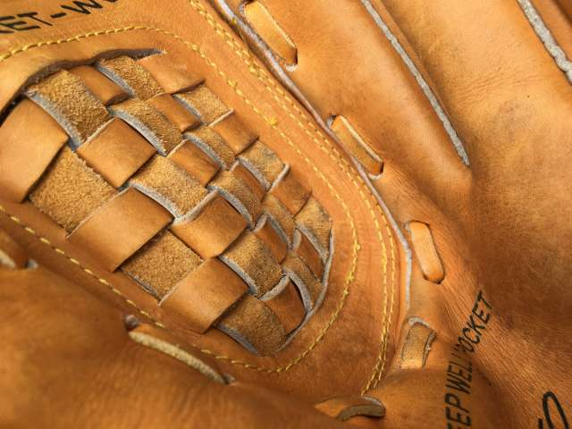The inside of light brown-colored baseball glove with cross-woven stitching.