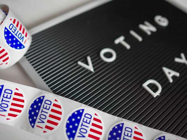 A black board shows the words, Voting Day, in a white font. The board is surrounded by round, I VOTED, stickers.